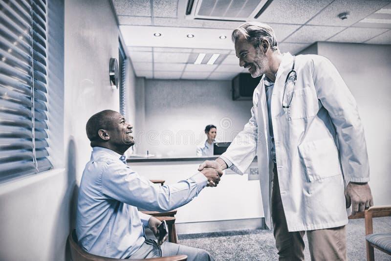 Manlig doktor som skakar händer med patienten royaltyfri bild