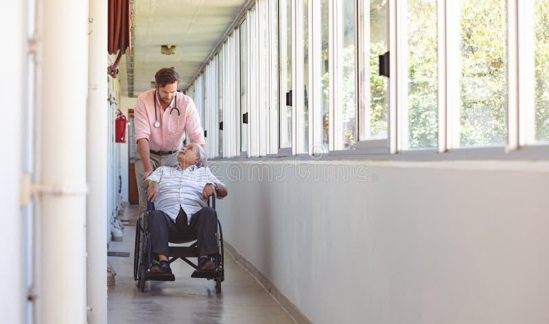 Manlig doktor som skjuter den höga rullstolmannen arkivfoto