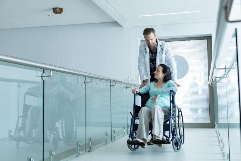 Manlig doktor som skjuter gravida kvinnan på rullstolen i korridoren royaltyfria bilder