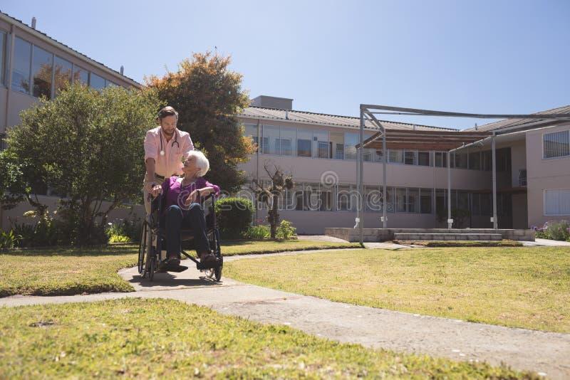 Manlig doktor som talar med höga tålmodiga kvinnor för handikappade personer i rullstol arkivbild