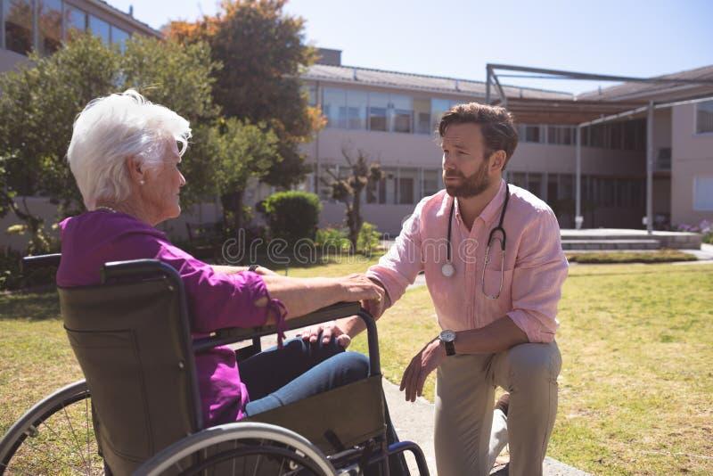 Manlig doktor som talar med h?ga t?lmodiga kvinnor f?r handikappade personer i rullstol royaltyfria foton