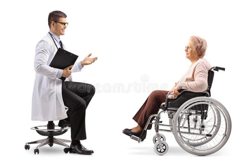 Manlig doktor som talar till en mogen kvinnlig patient i en rullstol arkivfoton