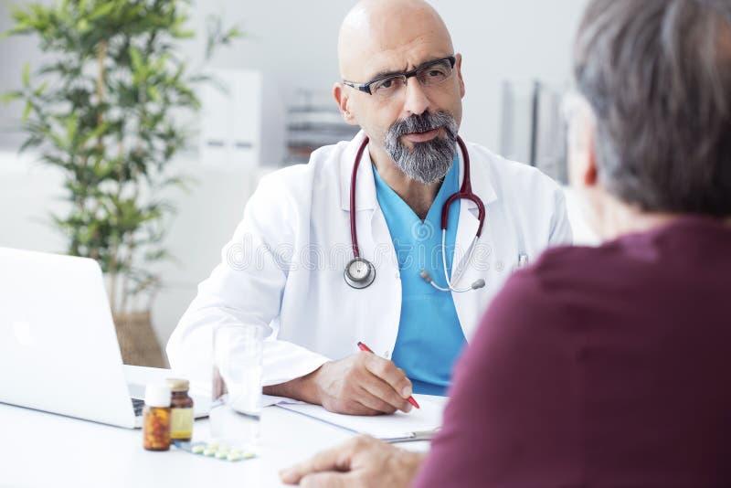 Manlig doktor som talar till patienten royaltyfria foton
