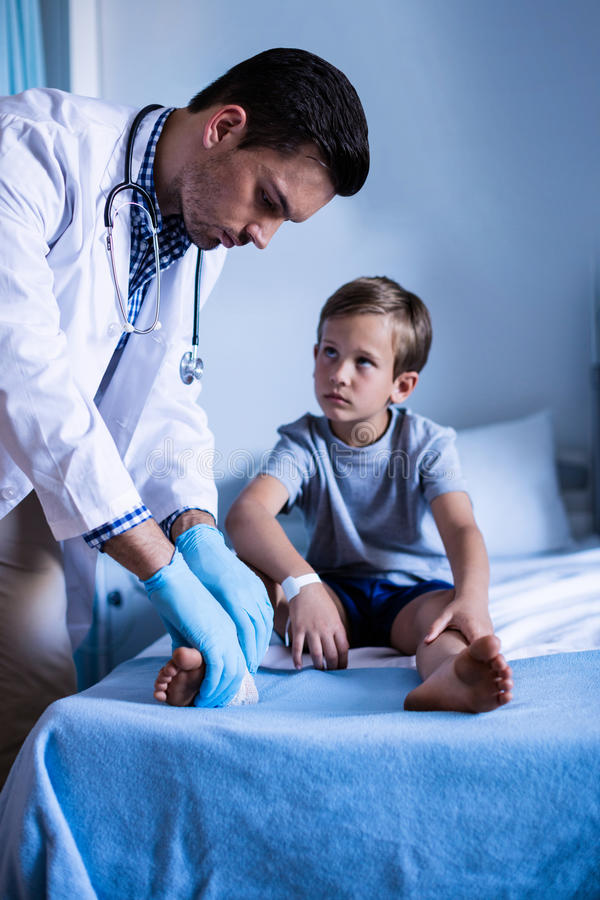 Manlig doktor som undersöker det tålmodiga benet arkivfoton