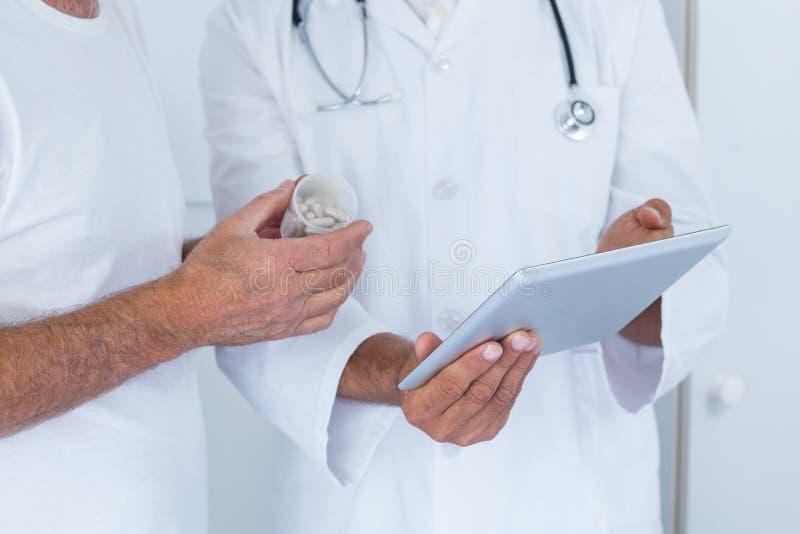 Manlig doktor som visar medicinska rapporter till den höga mannen på den digitala minnestavlan royaltyfri foto