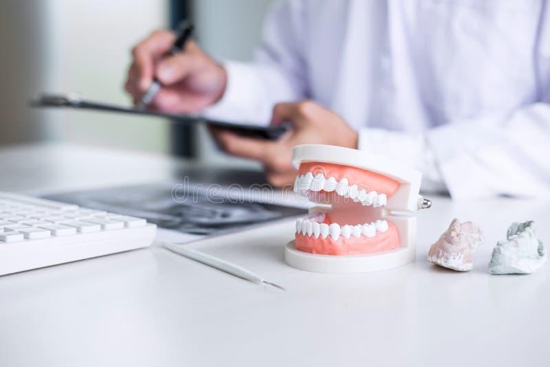 Manlig doktors- eller tandläkarehandstilrapport som arbetar med tandröntgenstråle f arkivfoto