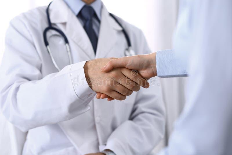Manlig doktors- och kvinnapatient som skakar händer Partnerskap i medicin, förtroende och begrepp för medicinska etik royaltyfri bild