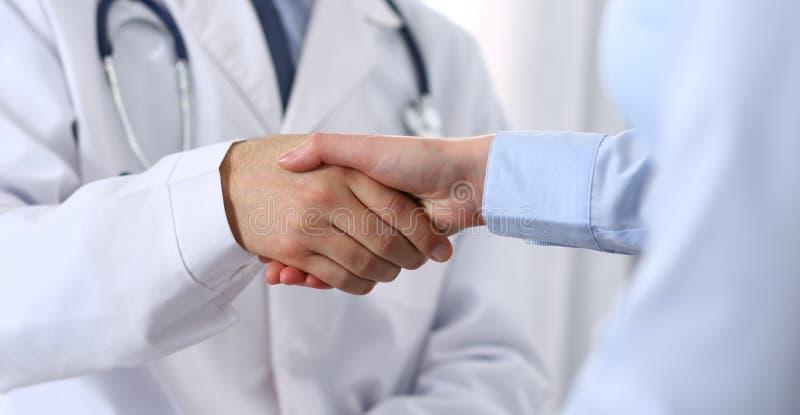 Manlig doktors- och kvinnapatient som skakar händer Partnerskap i medicin, förtroende och begrepp för medicinska etik royaltyfri foto