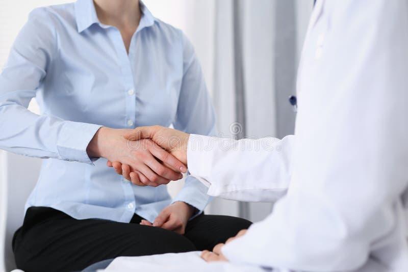 Manlig doktors- och kvinnapatient som skakar h?nder Partnerskap i medicin, f?rtroende och begrepp f?r medicinska etik arkivfoto