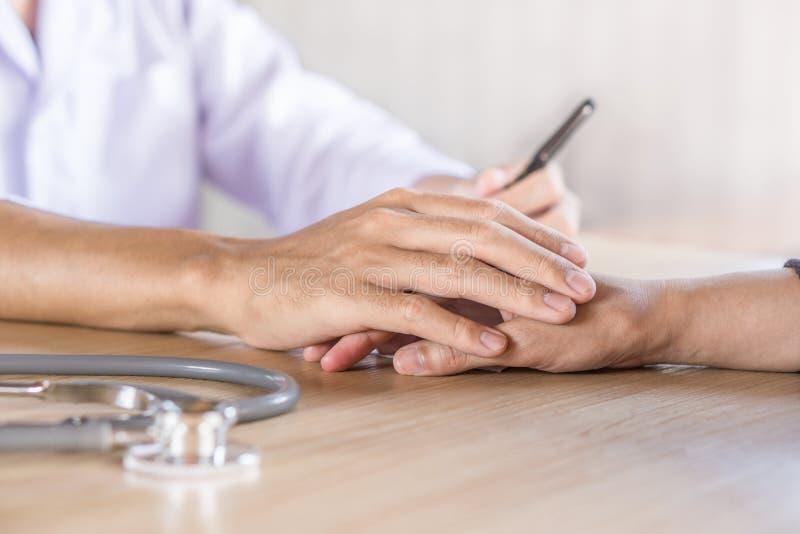 Manlig doktorsinnehavhand och tröstapatient i ett sjukhus royaltyfria bilder