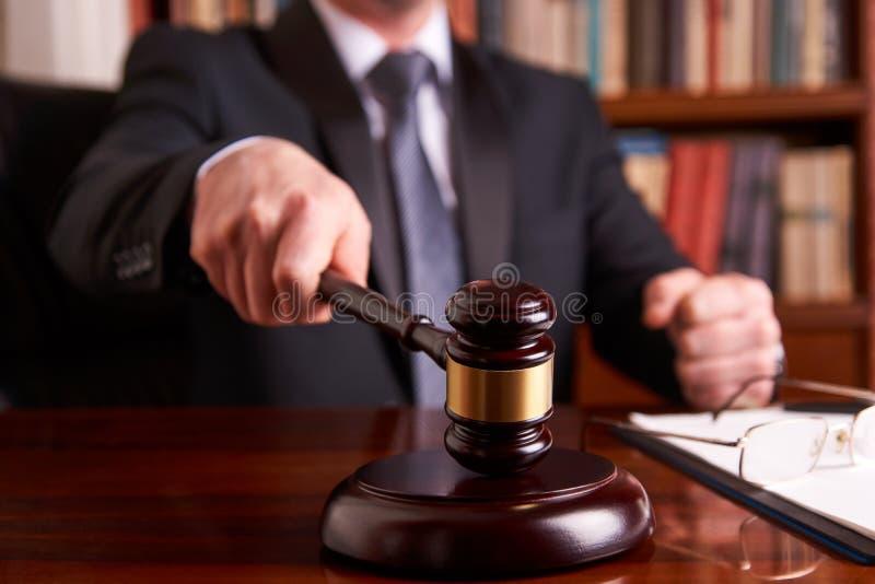 Manlig domare In en rättssal som slår auktionsklubban arkivbild