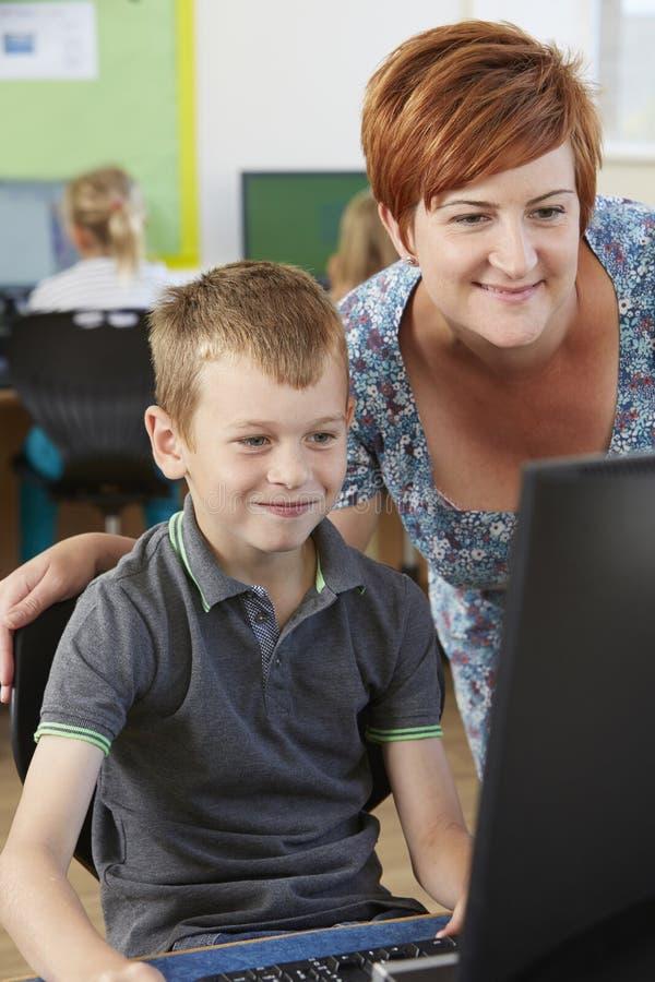 Manlig elementär elev i datorgrupp med läraren arkivfoto