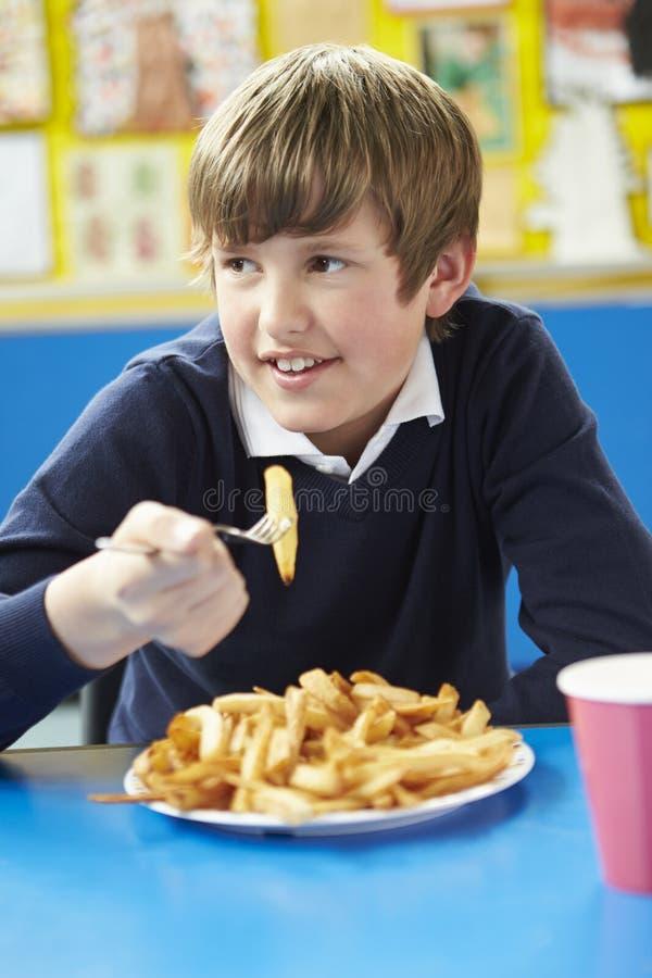 Manlig elev som äter sjuklig skolalunch arkivbild