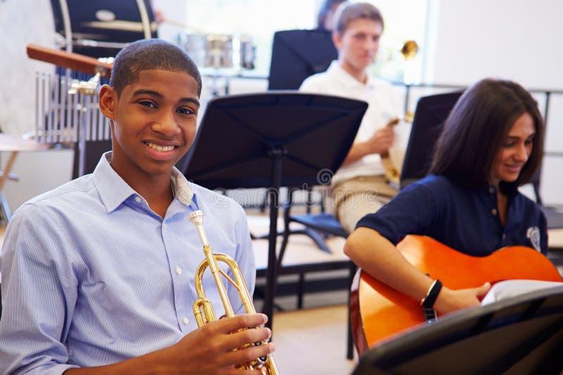 Manlig elev som spelar trumpeten i högstadiumorkester royaltyfria bilder
