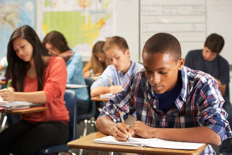 Manlig elev som studerar på skrivbordet i klassrum arkivfoton