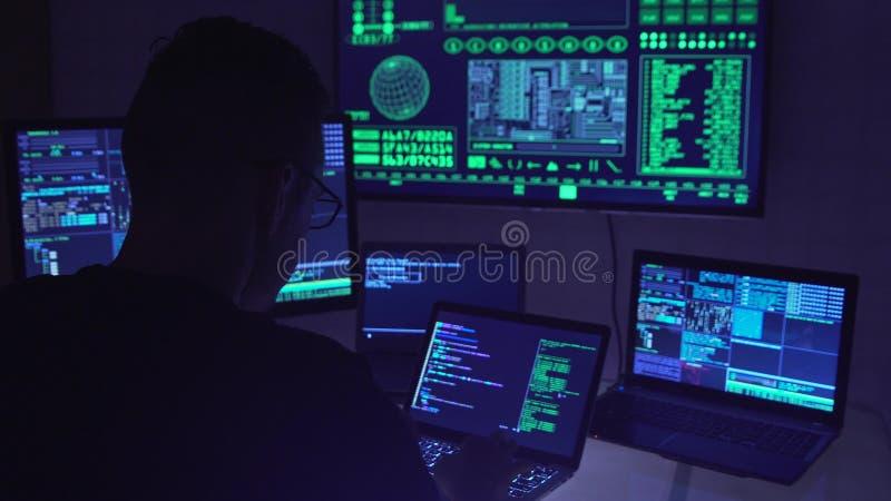Manlig en hacker som arbetar på en dator i ett mörkt kontorsrum arkivbilder