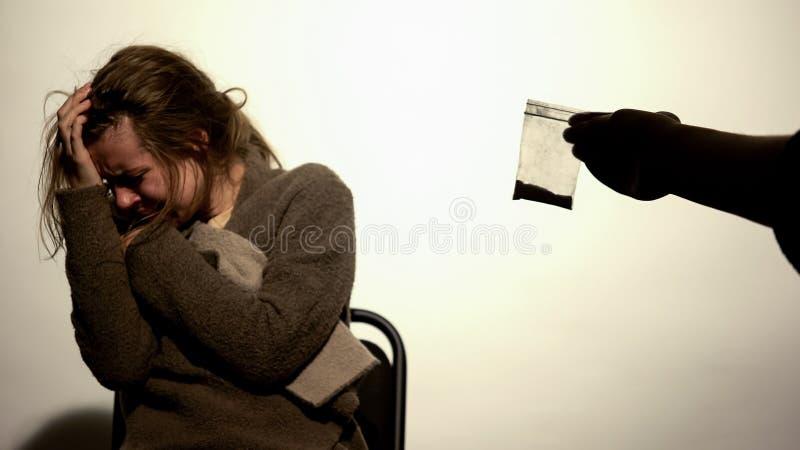 Manlig erbjudande kokain hemfallen kvinna, drogtillbakadragande, psykologiskt beroende royaltyfri foto