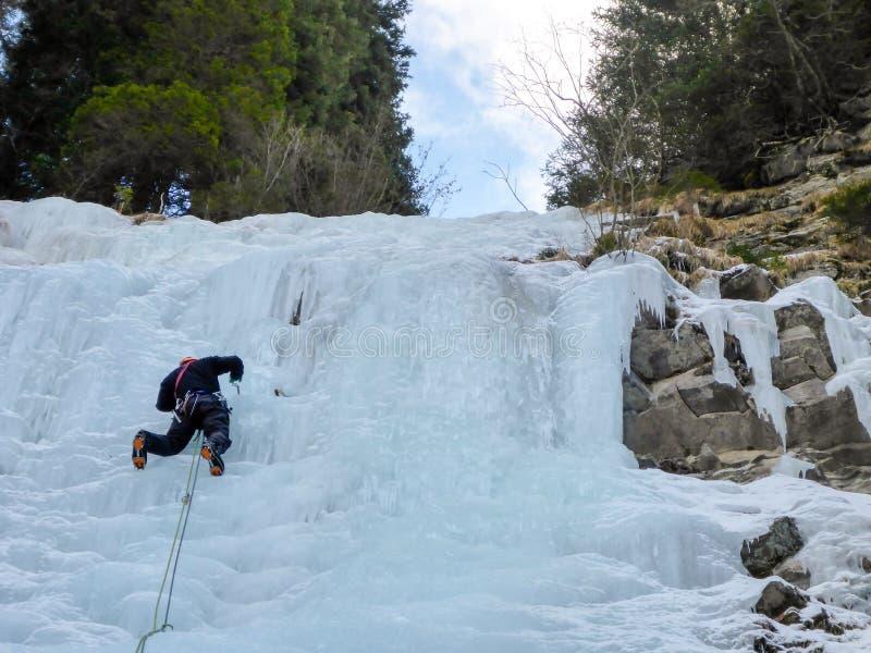 Manlig is för berghandbokledning som klättrar en djupfryst vattenfall i djup vinter i fjällängarna av Schweiz arkivfoto