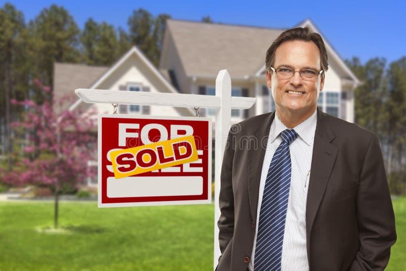 Manlig fastighetsmäklare framme av Sold tecknet och huset arkivbilder