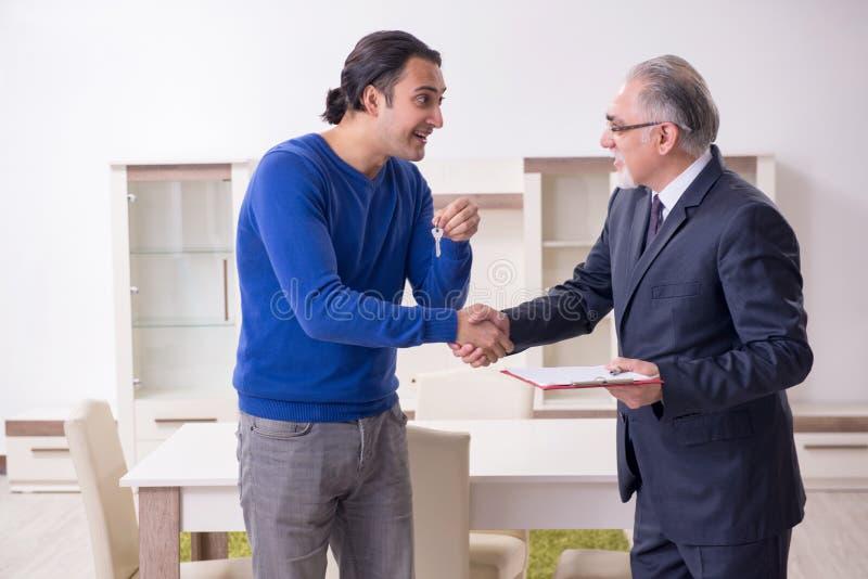 Manlig fastighetsmäklare och manlig klient i lägenheten royaltyfri bild