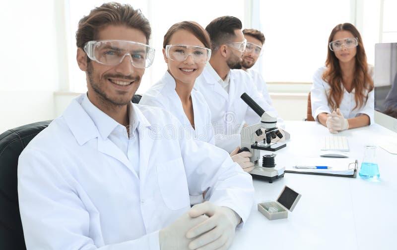 Manlig forskare och laget i labbet royaltyfri fotografi