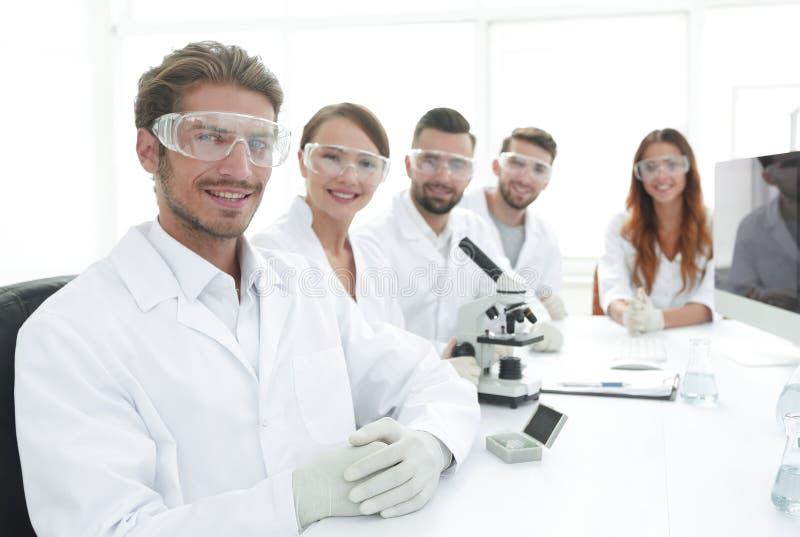 Manlig forskare och laget i labbet royaltyfri foto