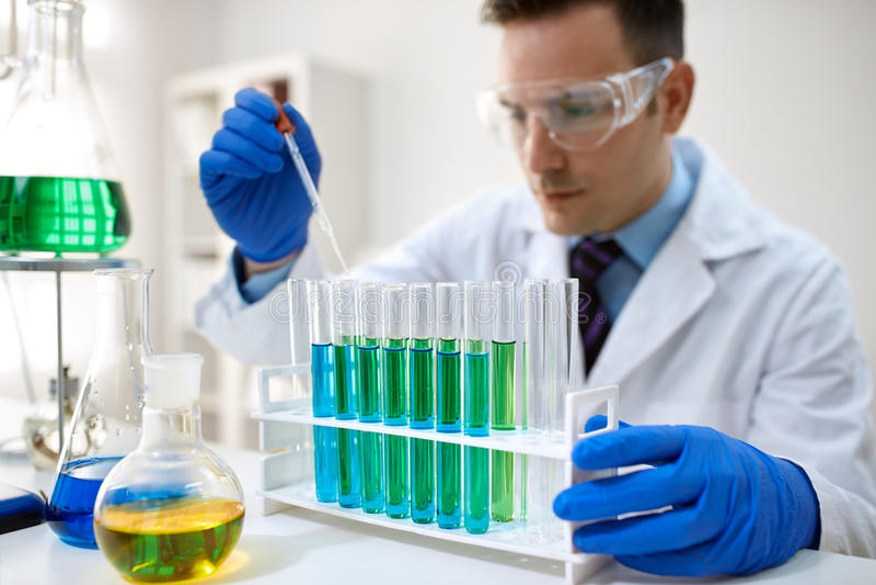 Manlig forskare som använder kemiflytande för forskning arkivfoton