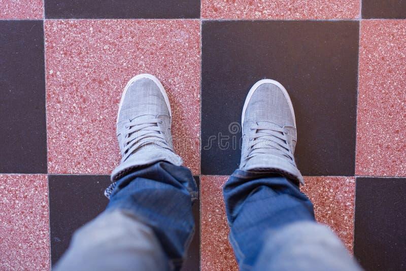 Manlig fot i jeans och gymnastikskor i köket arkivbild
