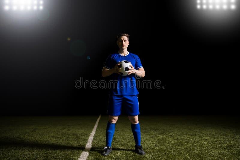Manlig fotbollsspelare i blå likformig på fotbollfält royaltyfria foton