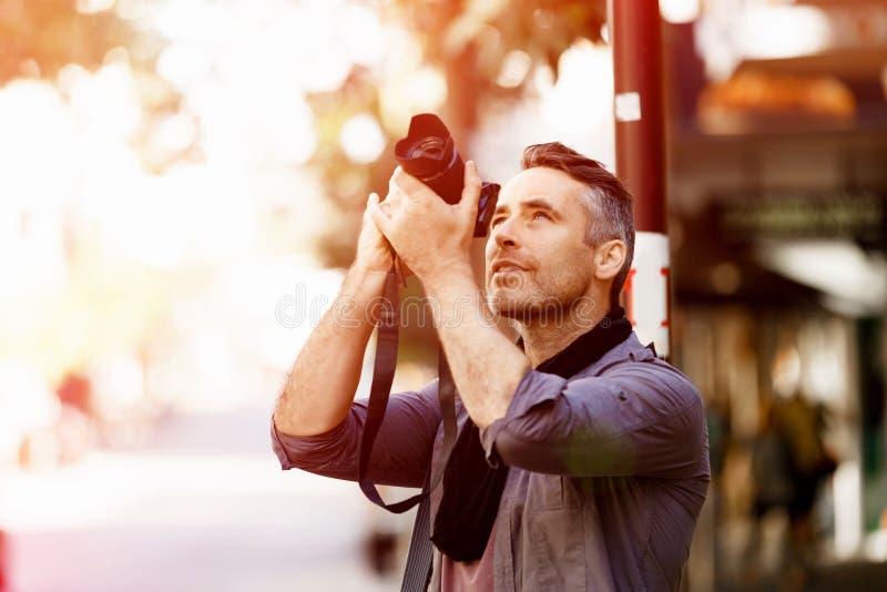Manlig fotograf som tar bilden arkivbild