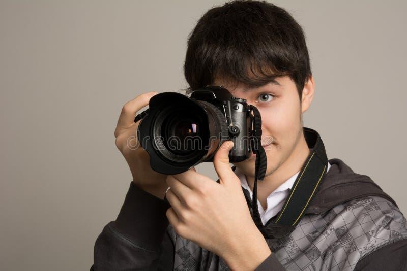 Manlig fotograf som tar foto med den digitala kameran för DSLR arkivfoto