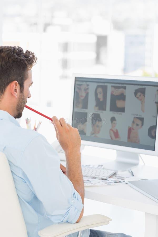 Manlig fotoredaktör som i regeringsställning arbetar på datoren arkivfoto