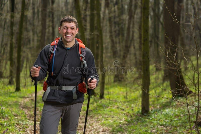 Manlig fotvandrare som ser till sidan som går i skog arkivbild
