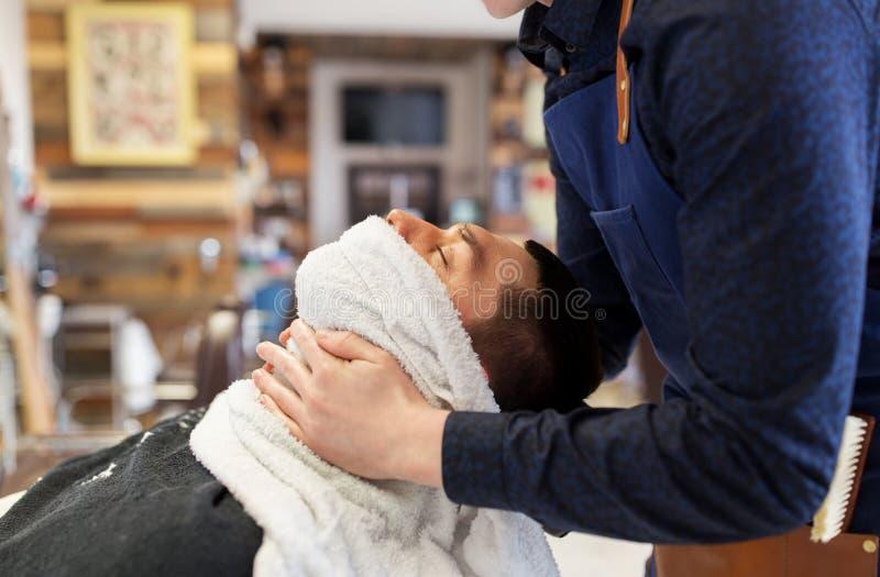 Manlig framsida för barberareuppmjukning som sking med den varma handduken royaltyfri foto