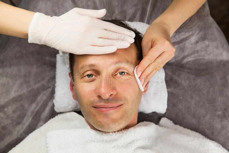Manlig framsida, händer av den yrkesmässiga kosmetologen med handskar fotografering för bildbyråer