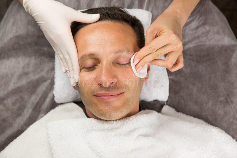 Manlig framsida, händer av den yrkesmässiga kosmetologen med handskar royaltyfria bilder