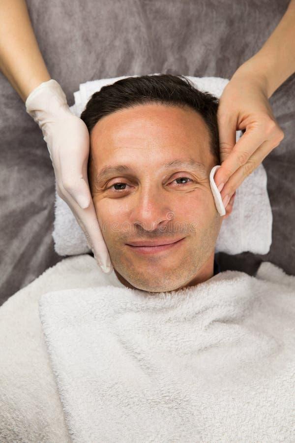 Manlig framsida, händer av den yrkesmässiga kosmetologen med handskar arkivfoton