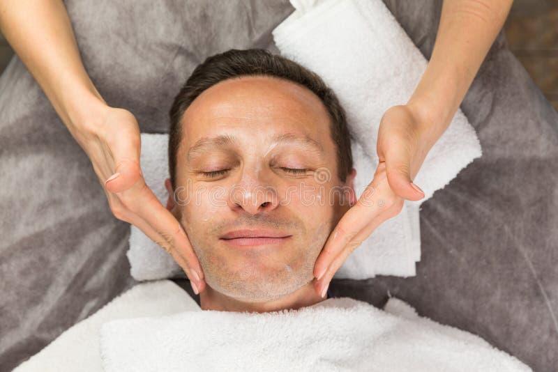 Manlig framsida med den kräm- maskeringen, händer av den yrkesmässiga kosmetologen royaltyfria bilder