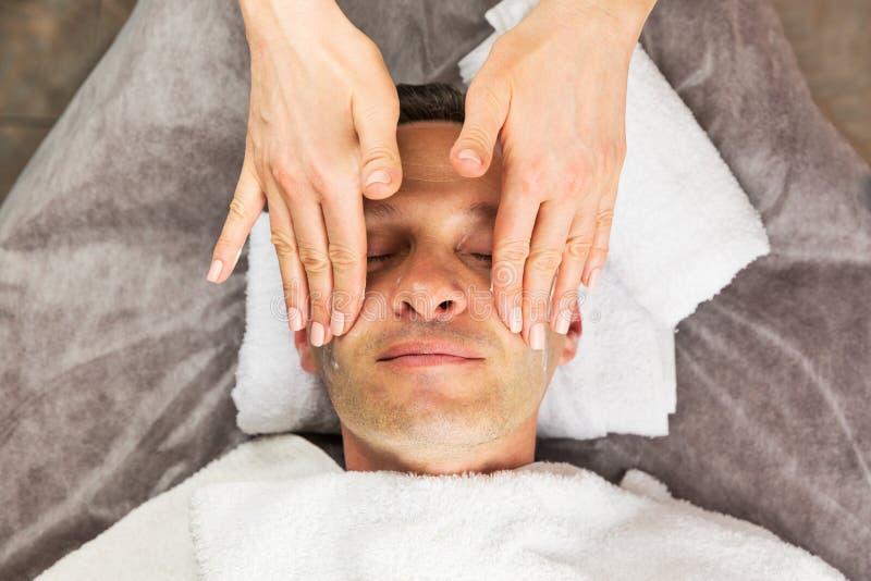 Manlig framsida med den kräm- maskeringen, händer av den yrkesmässiga kosmetologen arkivfoton