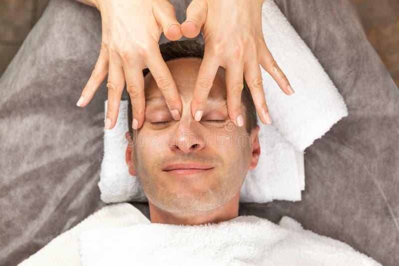 Manlig framsida med den kräm- maskeringen, händer av den yrkesmässiga kosmetologen royaltyfri foto