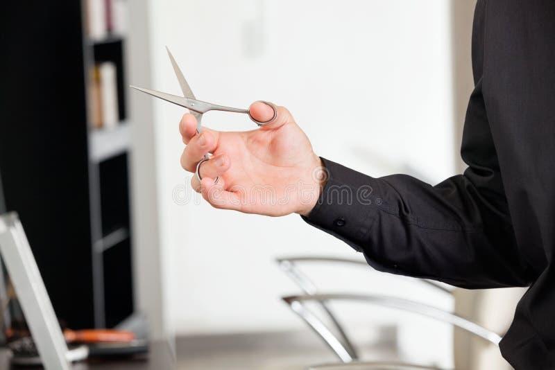 Manlig frisörs hållande sax för hand royaltyfri foto