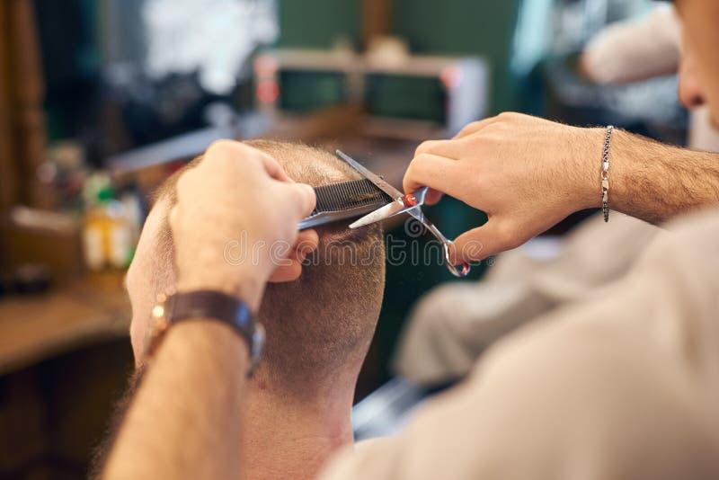 Manlig fris?r som g?r kort frisyr f?r klient i modern frisersalong Begrepp av traditionell haircutting med sax royaltyfri fotografi