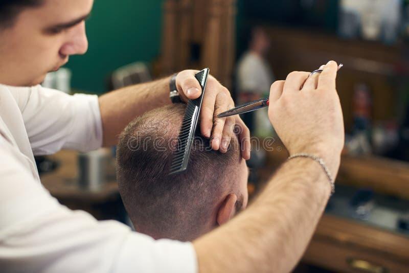 Manlig fris?r som g?r kort frisyr f?r klient i modern frisersalong Begrepp av traditionell haircutting med sax arkivbilder