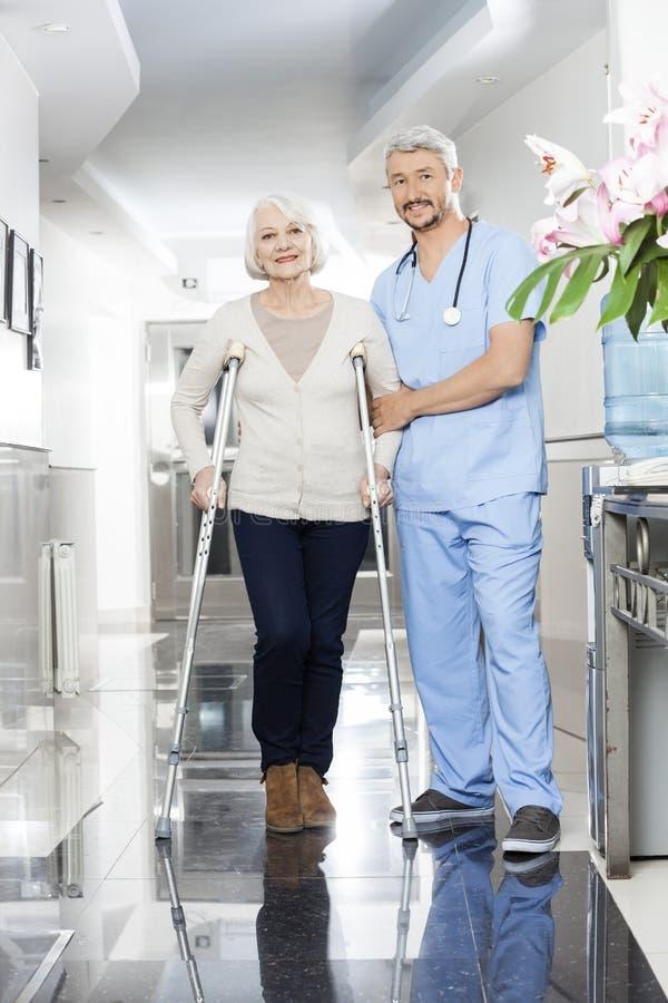 Manlig fysioterapeut Helping Senior Woman med kryckor royaltyfri bild