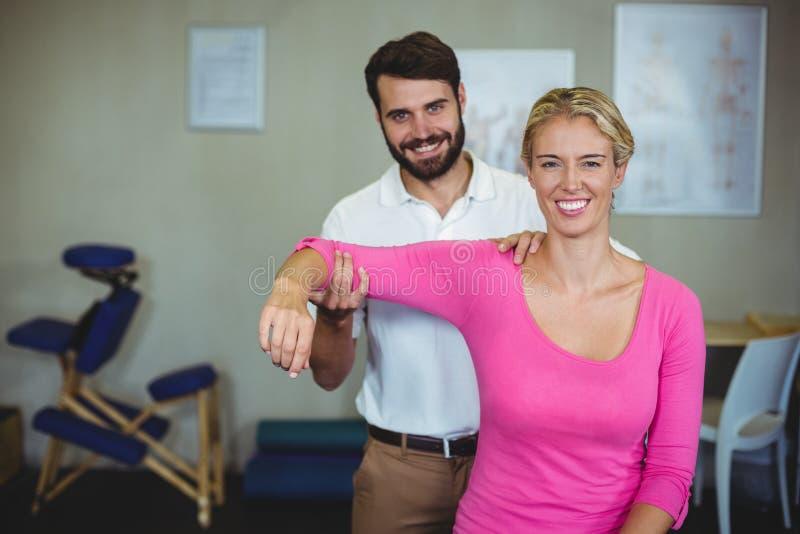 Manlig fysioterapeut som ger armmassage till den kvinnliga patienten royaltyfri bild