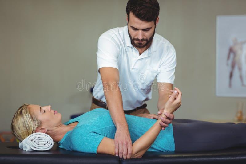 Manlig fysioterapeut som ger armmassage till den kvinnliga patienten fotografering för bildbyråer