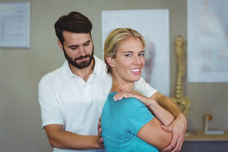 Manlig fysioterapeut som ger armmassage till den kvinnliga patienten arkivfoto