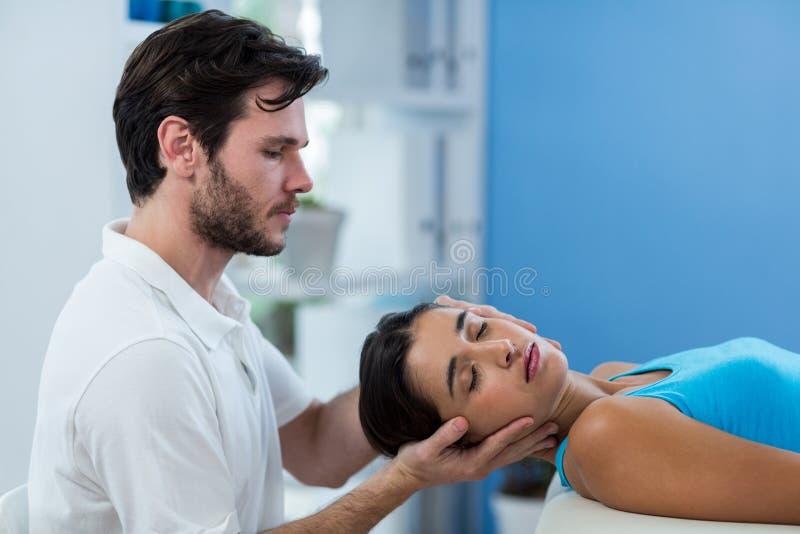 Manlig fysioterapeut som ger den head massagen till den kvinnliga patienten arkivbilder