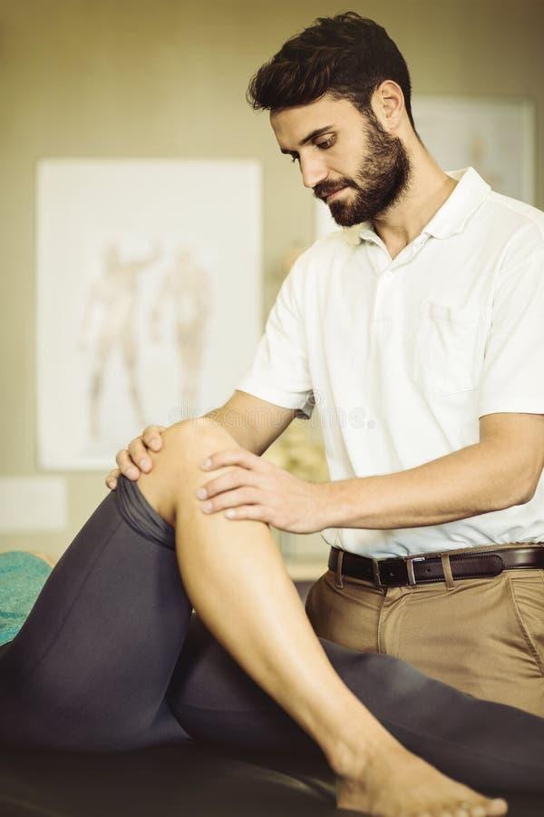 Manlig fysioterapeut som ger knämassage till den kvinnliga patienten arkivfoto