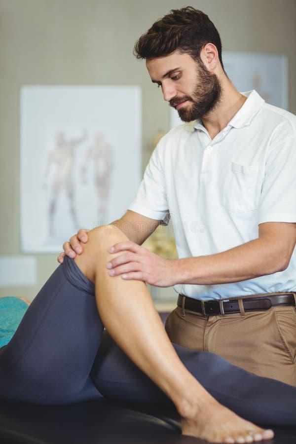 Manlig fysioterapeut som ger knämassage till den kvinnliga patienten fotografering för bildbyråer